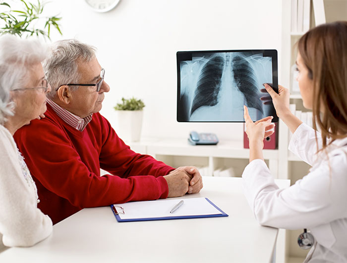 older adult woman and man looking at xray with doctor