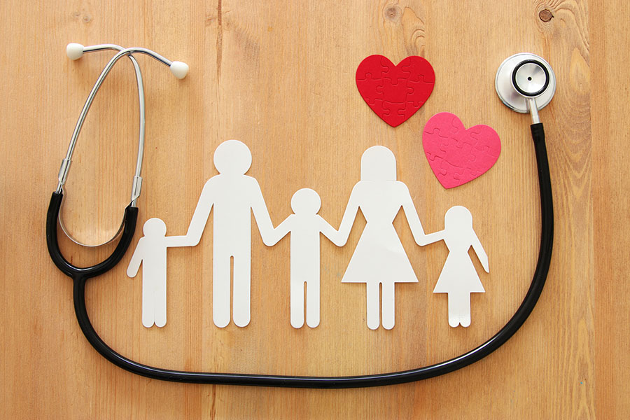 paper cutout of family surrounded by stethoscope